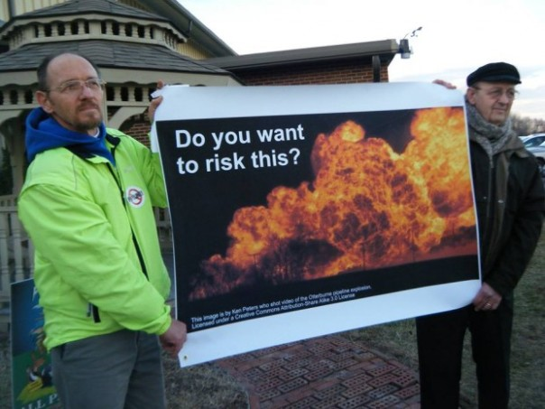 Steve Yoder (left) and Charlie Strickler (right) hold picture of pipeline explosion at Dominion meeting. Source: Friends of Augusta.