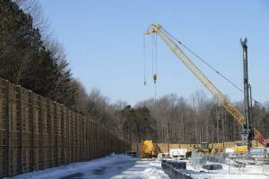 A temporary 20-foot wood sound wall has been erected to contain the noise of construction at the Cove Point LNG plant. The permanent 60-foot wall will be built just inside the current wall before the temporary one is torn down.
