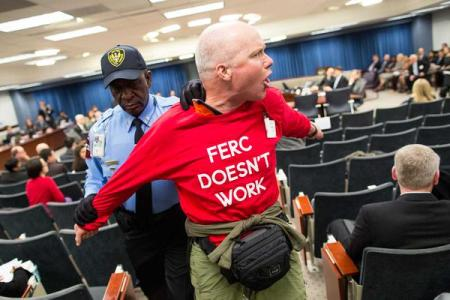 A protestor is escorted from the FERC Commissioners' meeting on March 19, 2015/Photo by Scott Mahaskey