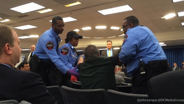 Federal Protective Services officers pull Ted Glick out of his seat at FERC meeting.